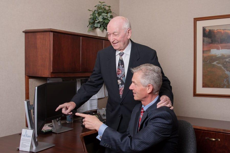 Clark And Paul Pointing At Computer At Lake Region Bank