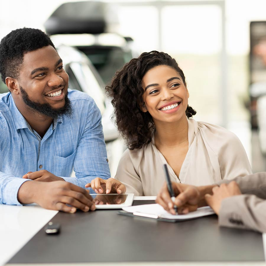 Couple Buying Car Signing Papers With Salesman In Dealership Office