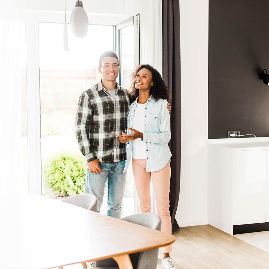 African American Couple Hugging And Looking At Room