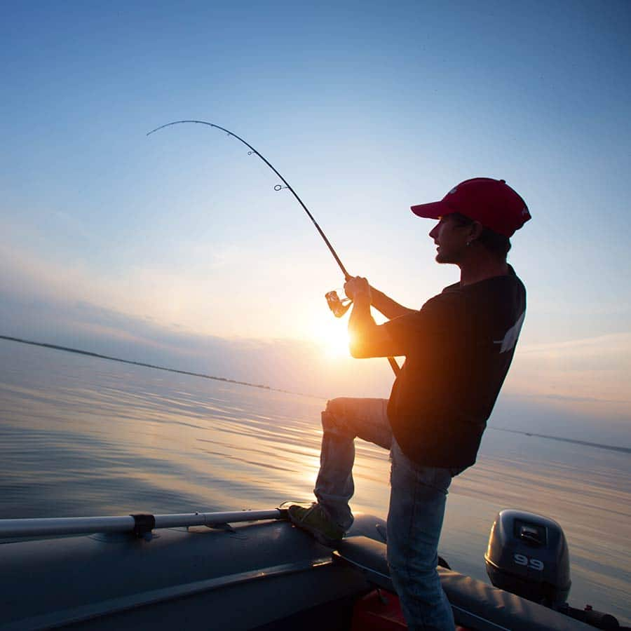 Holding Fishing Pole In Boat At Sunset