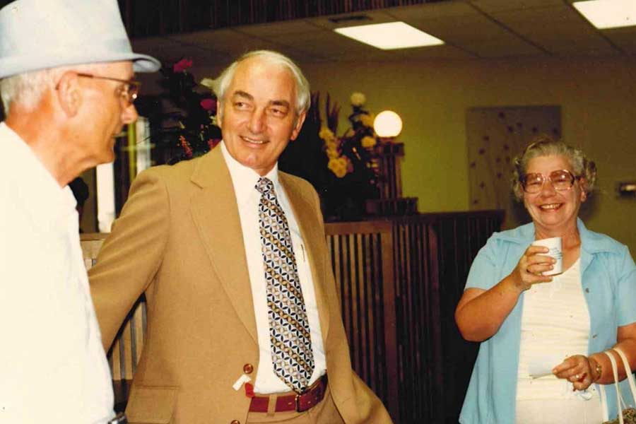 Paul Vollan enjoying coffee with two Lake Region Bank customers in 1980