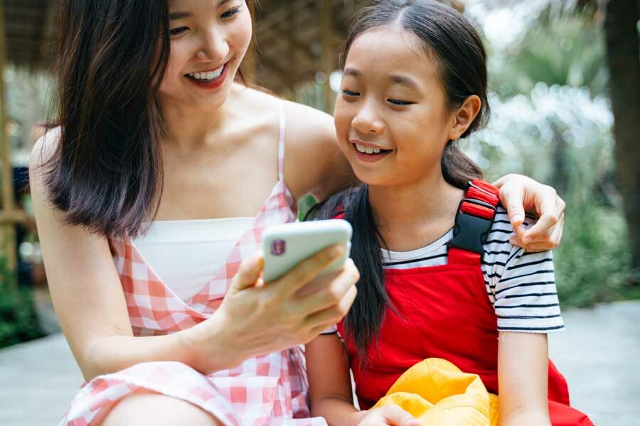 Cheerful Asian Family On Smartphone