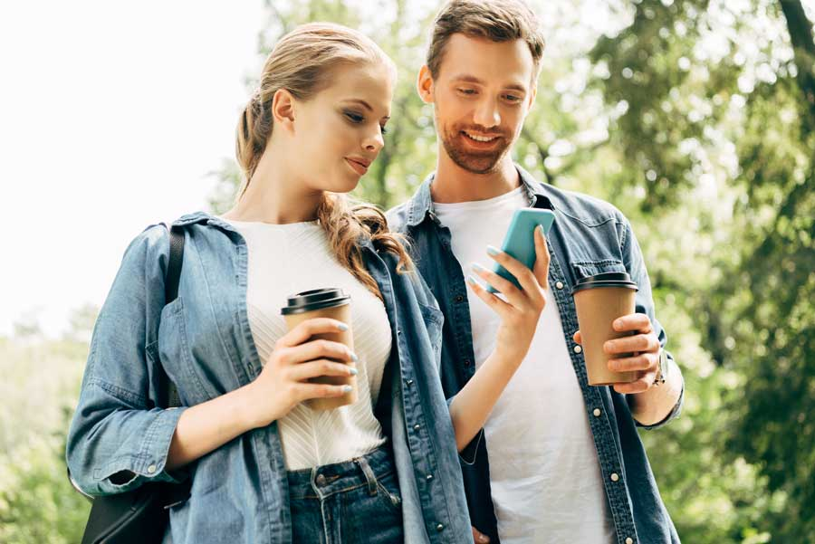 Young Couple With Coffee Using Smartphone Together At Park